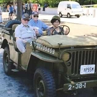 99veterans participated in the 2012 National memorial Day Parade. Joe Prola sits shotgun in a jeep while John McCoy sits in the back and a spectator rushes ahead of the parked jeep to take a picture of his wife, behind the wheel.